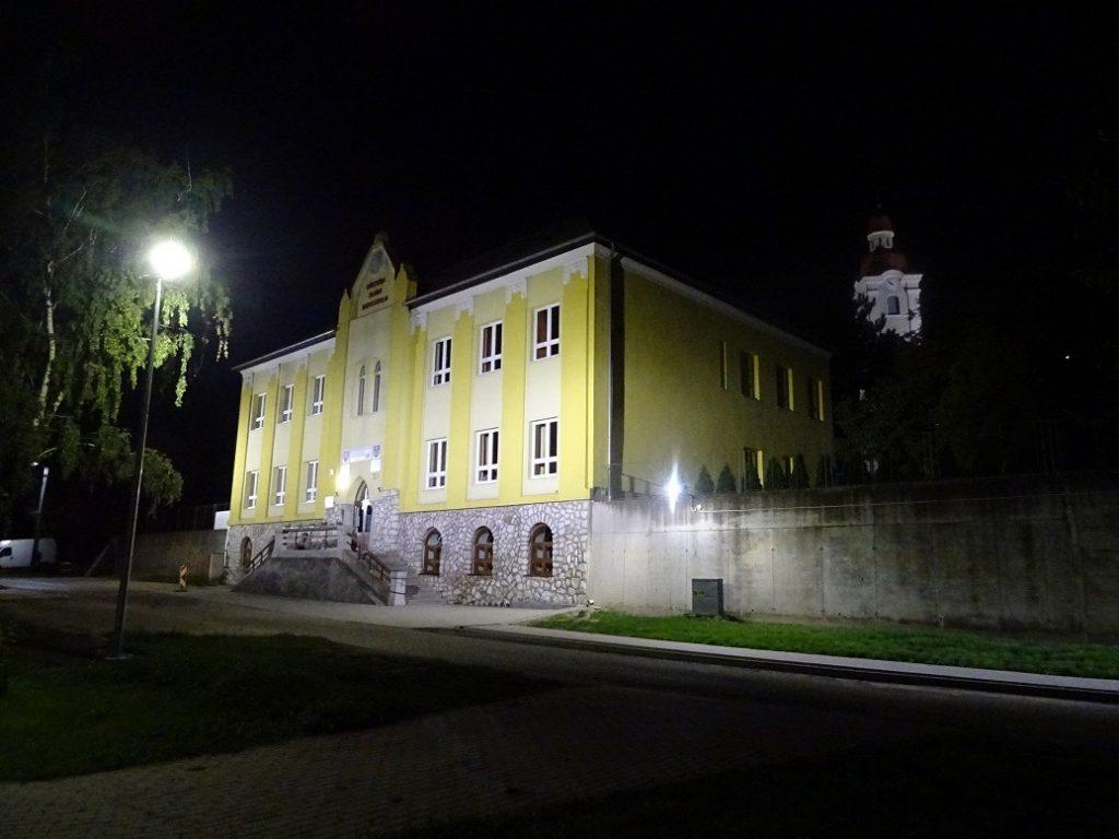 Nočné osvetlenie historickej budovy základnej školy a parku v Mužle